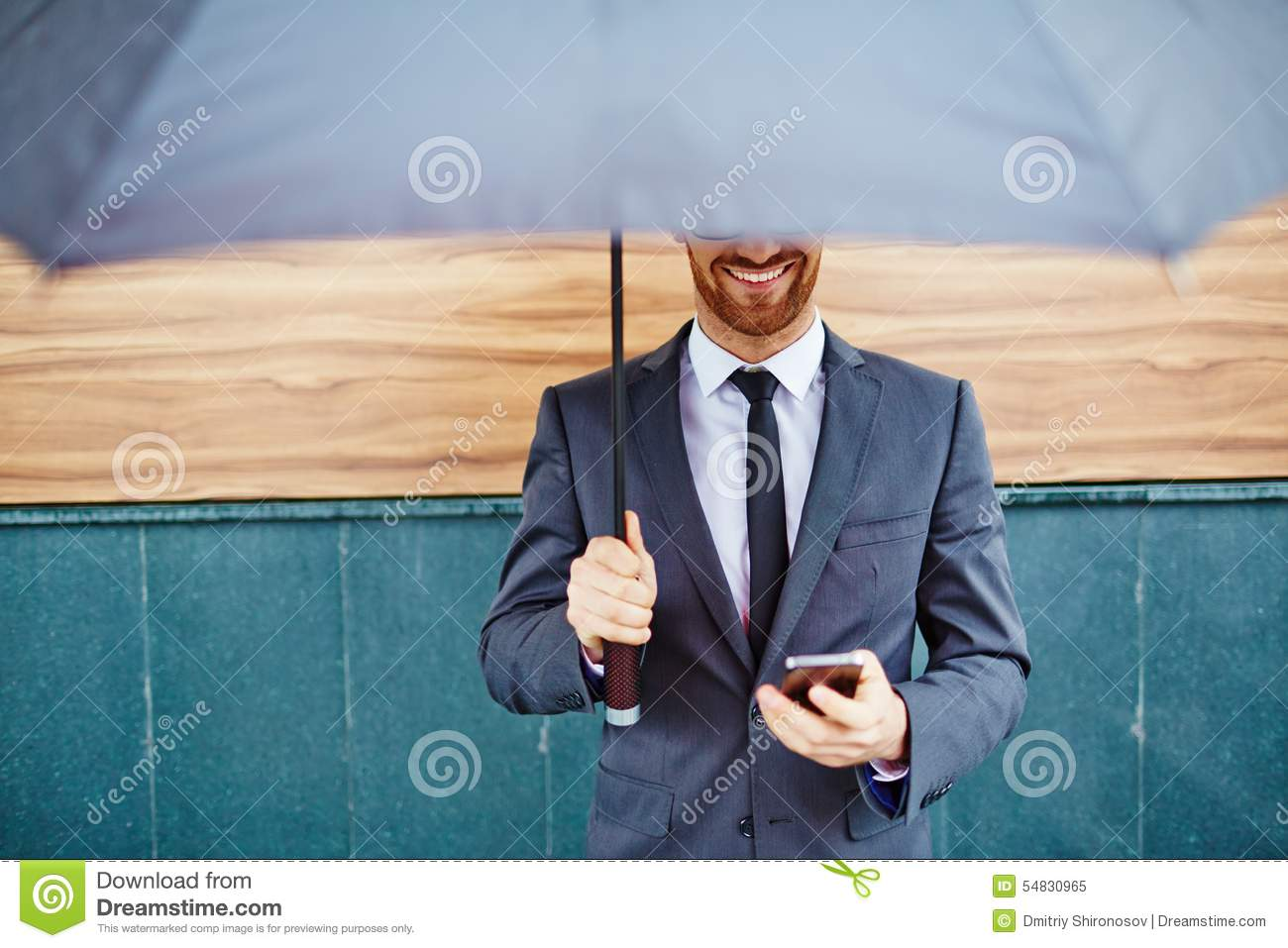 entrepreneur-under-umbrella-smiling-cellphone-standing-54830965