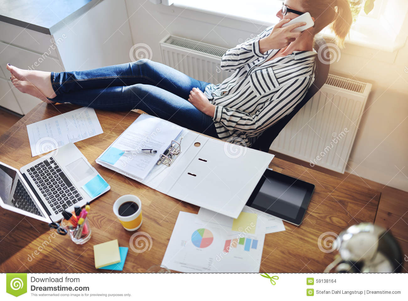 relaxed-confident-female-entrepreneur-reclining-back-her-chair-her-bare-feet-desk-talking-to-client-her-mobile-59138164